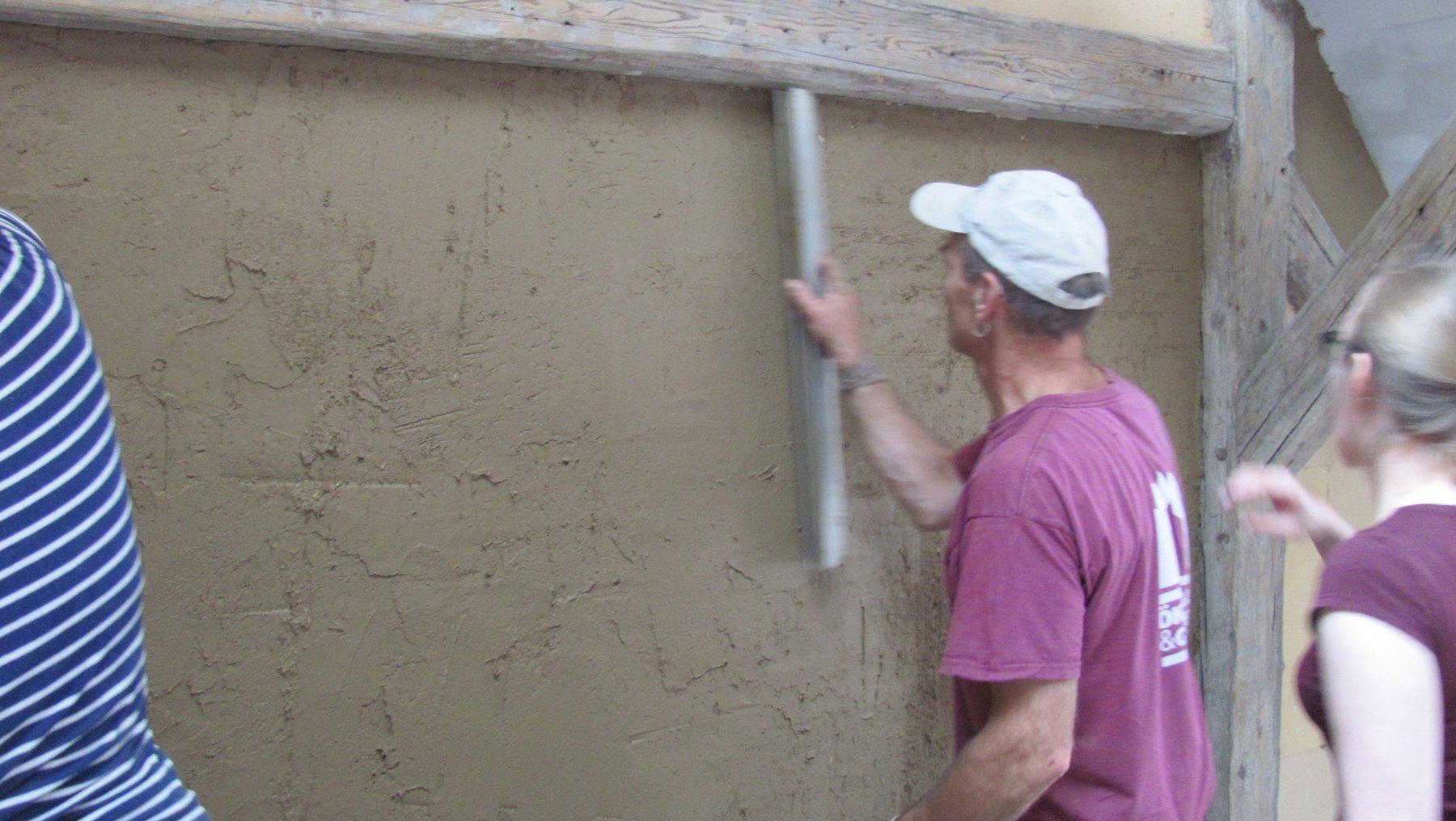 Lehmputzpraktikum - Student beim Veputzen einer Wand
