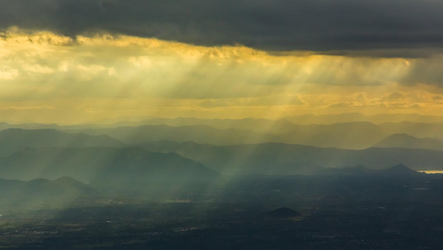 Bild aus der Vogelperspektive mit starkem Monsunregen über einem Tal mit Bergen im Hintergrund